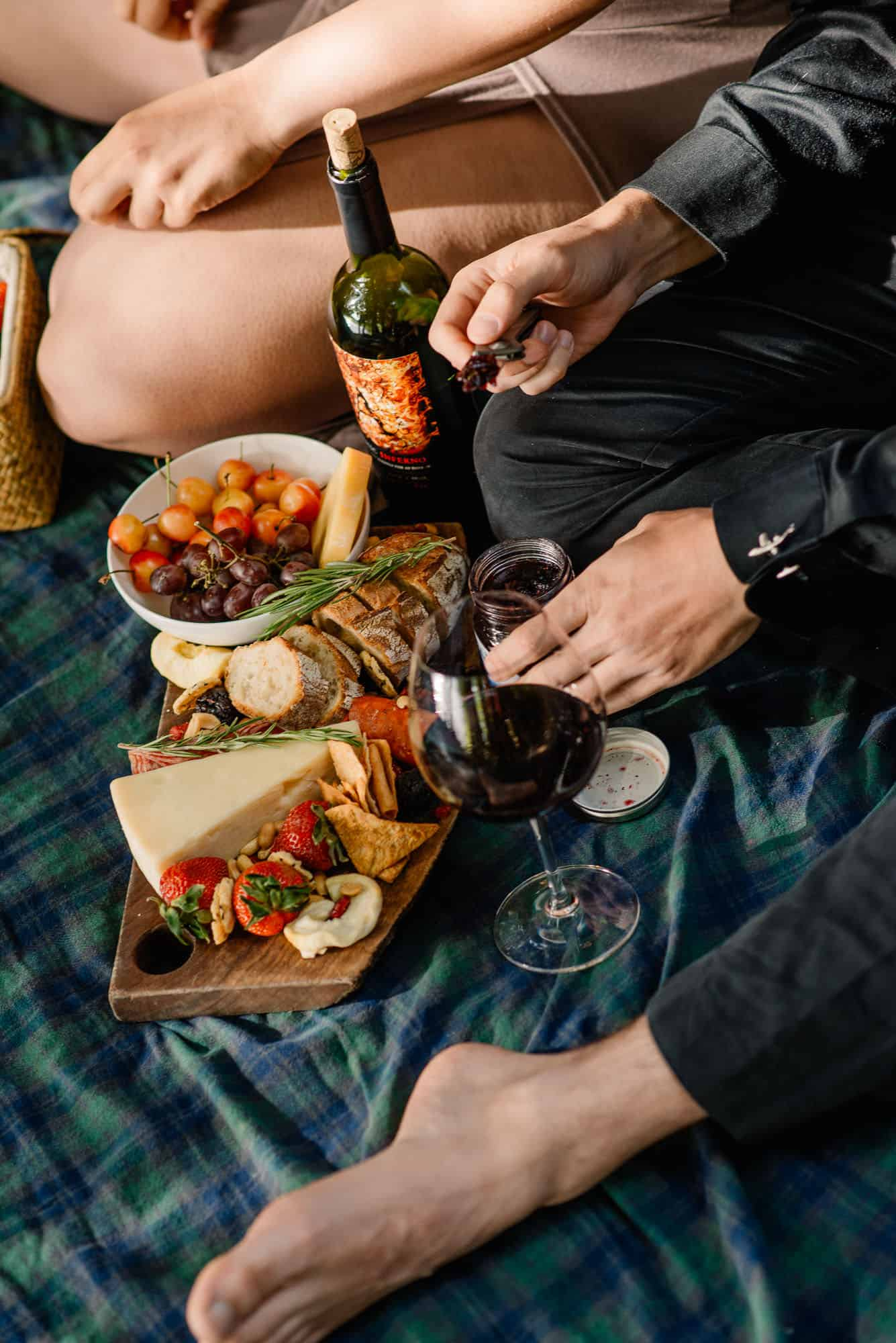 couple having a romantic picnic on a picnic blanket following this romantic thing to do in maui list