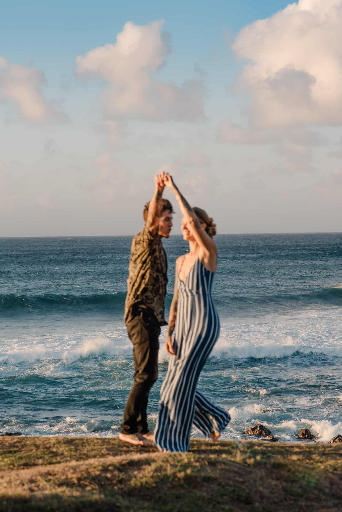 couple dancing near the beach at sunset as the sun glows golden on their skin