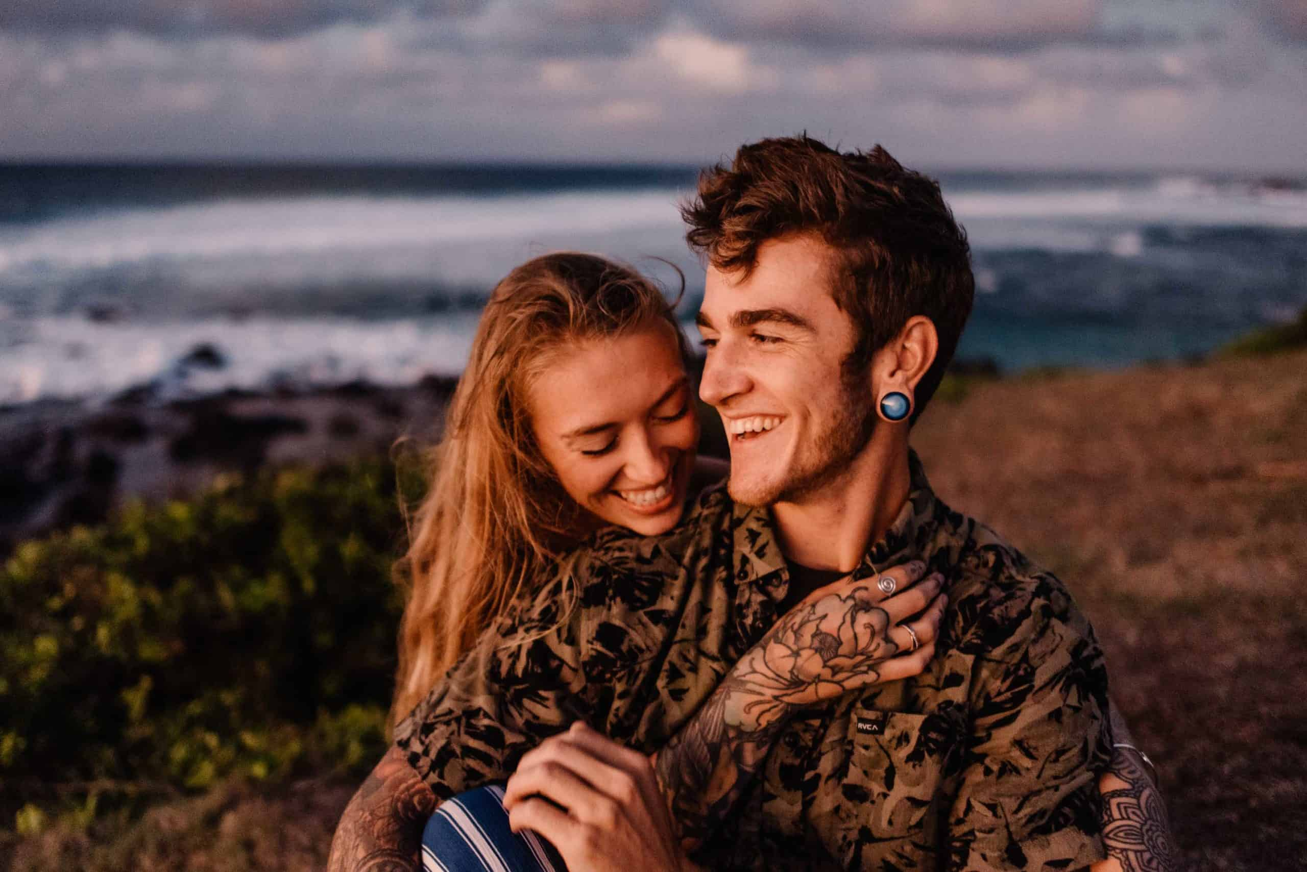 couple cuddling at sunset in Maui as they are laughing together enjoying a good time from following this romantic things to do in Maui list
