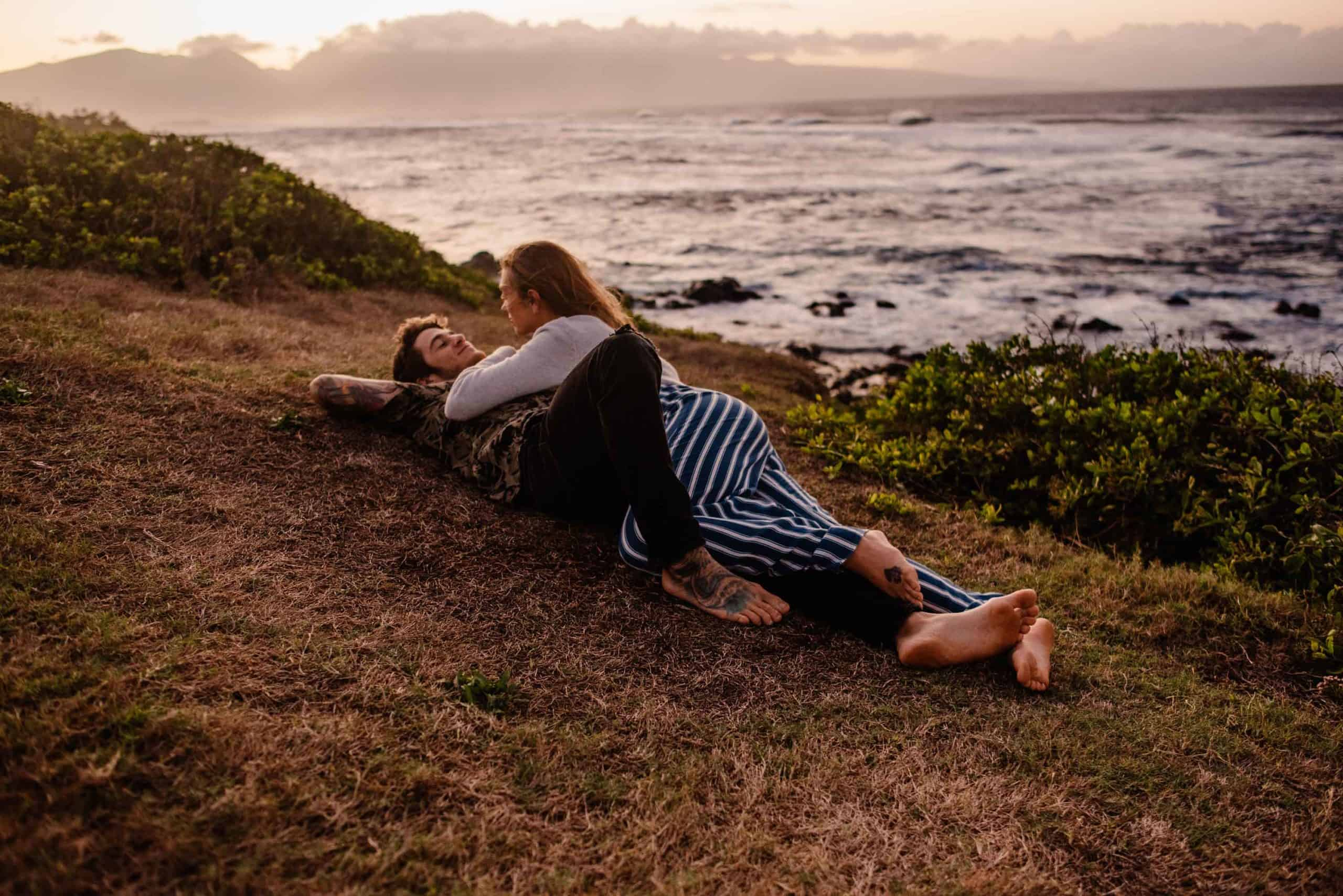 couple snuggling in the grass at a park in Maui