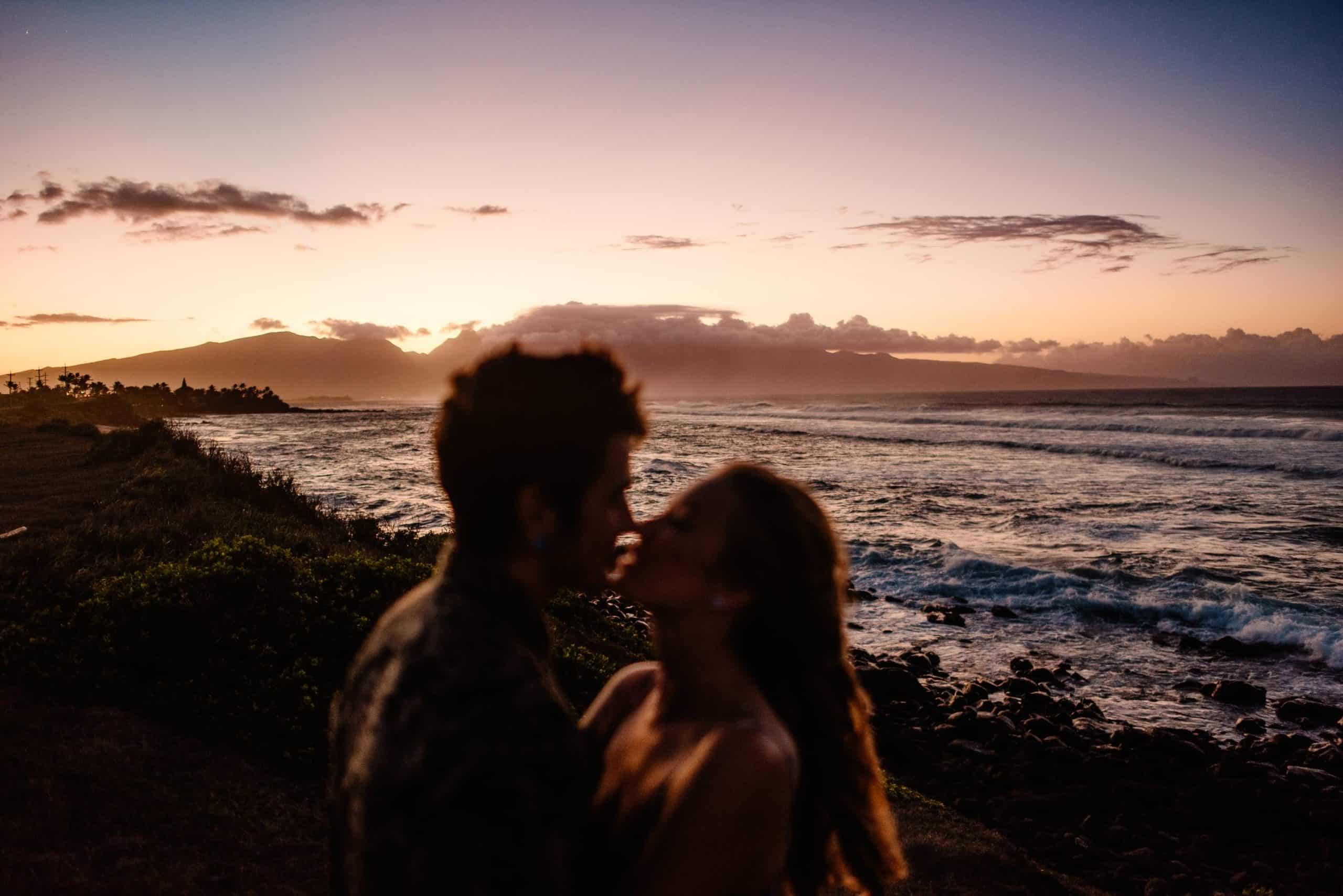 couple having a romantic time together at sunset as they followed our romantic things to do in maui guide and are kissing as the sunsets behind the Iao Valley on Maui