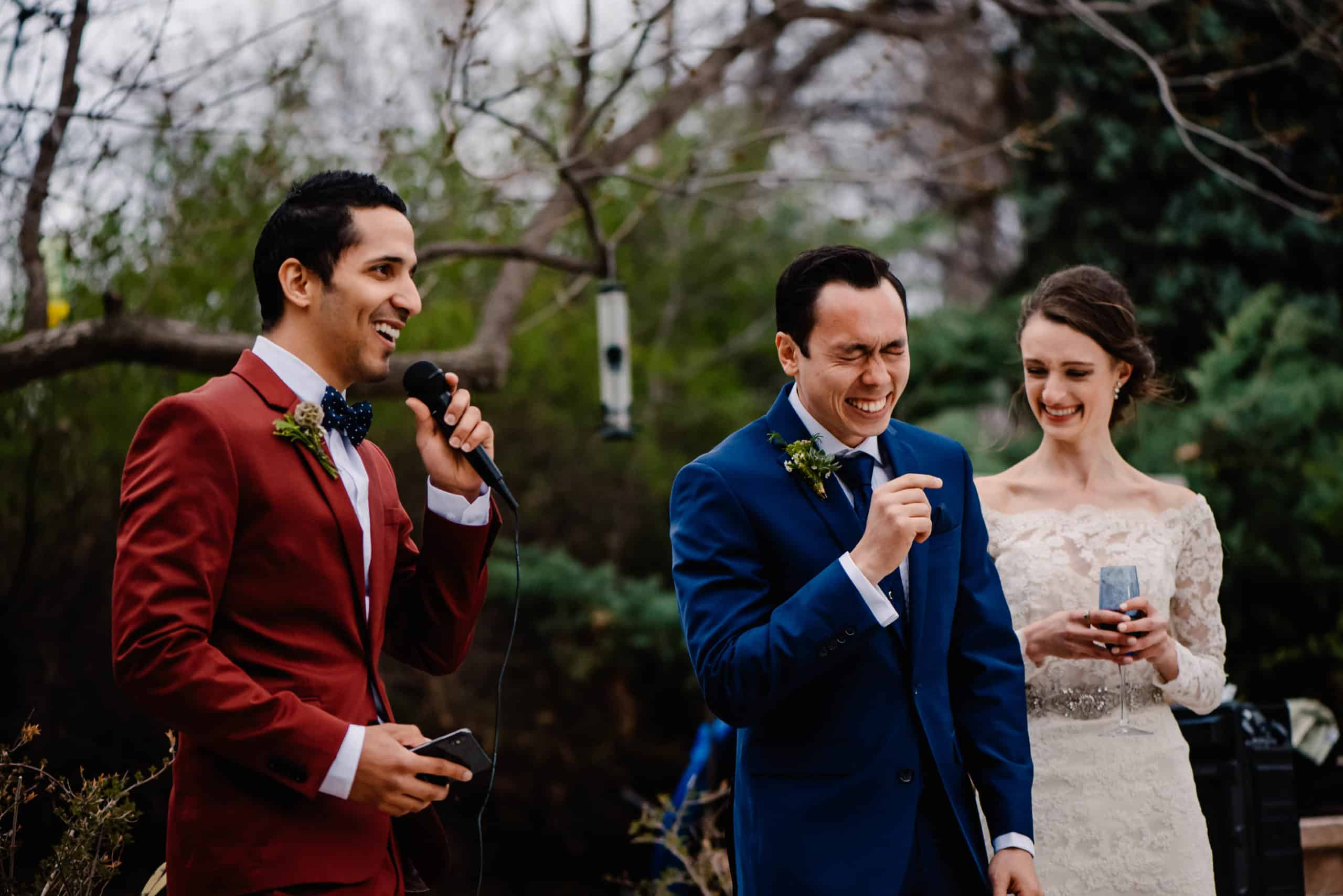 groom laughing as his best man gives a speech at his backyard airbnb wedding