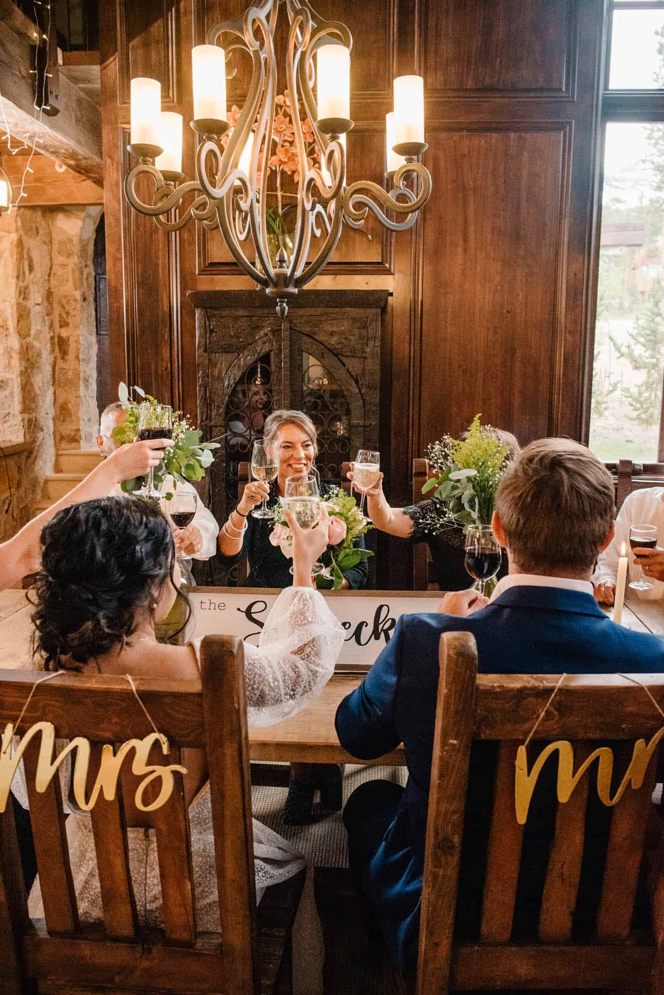 bride and groom sitting at the table with their family after their wedding ceremony at an airbnb wedding venue