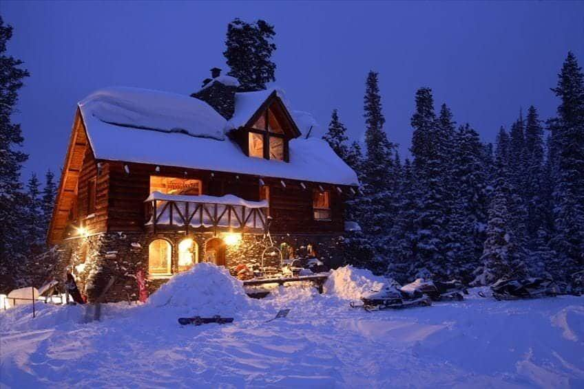 airbnb wedding venues colorado via verb a cabin in the woods with snow all around the lights turned on