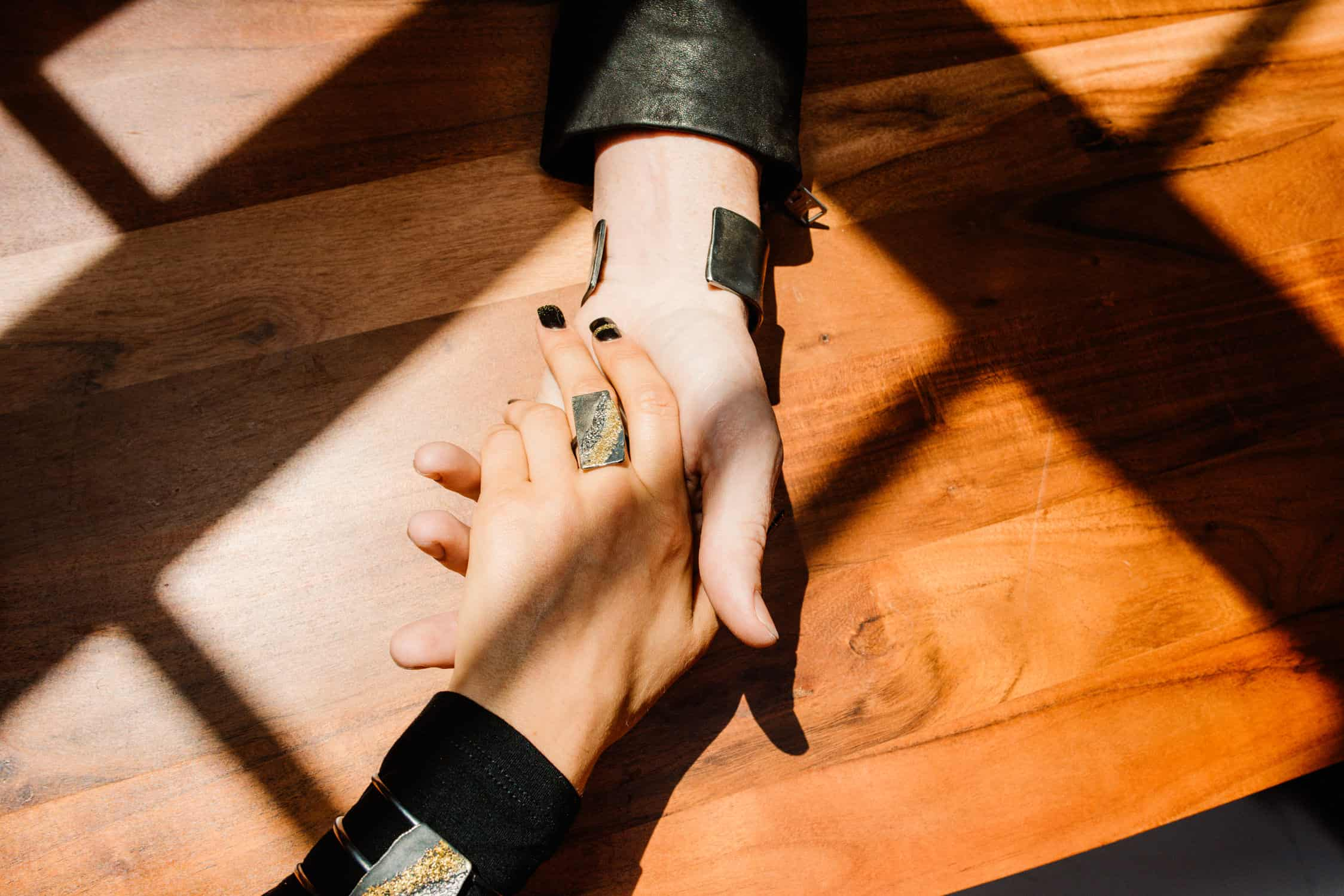 couple holding hands wearing jewelry, photos from a denver personal brand photoshoot of a jeweler's products