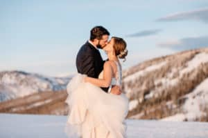 couple standing on a mountain top after their adventurous elopement