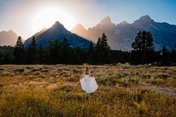 bride walking towards mountain as sunsets. She's happy that she is eloping during the pandemic