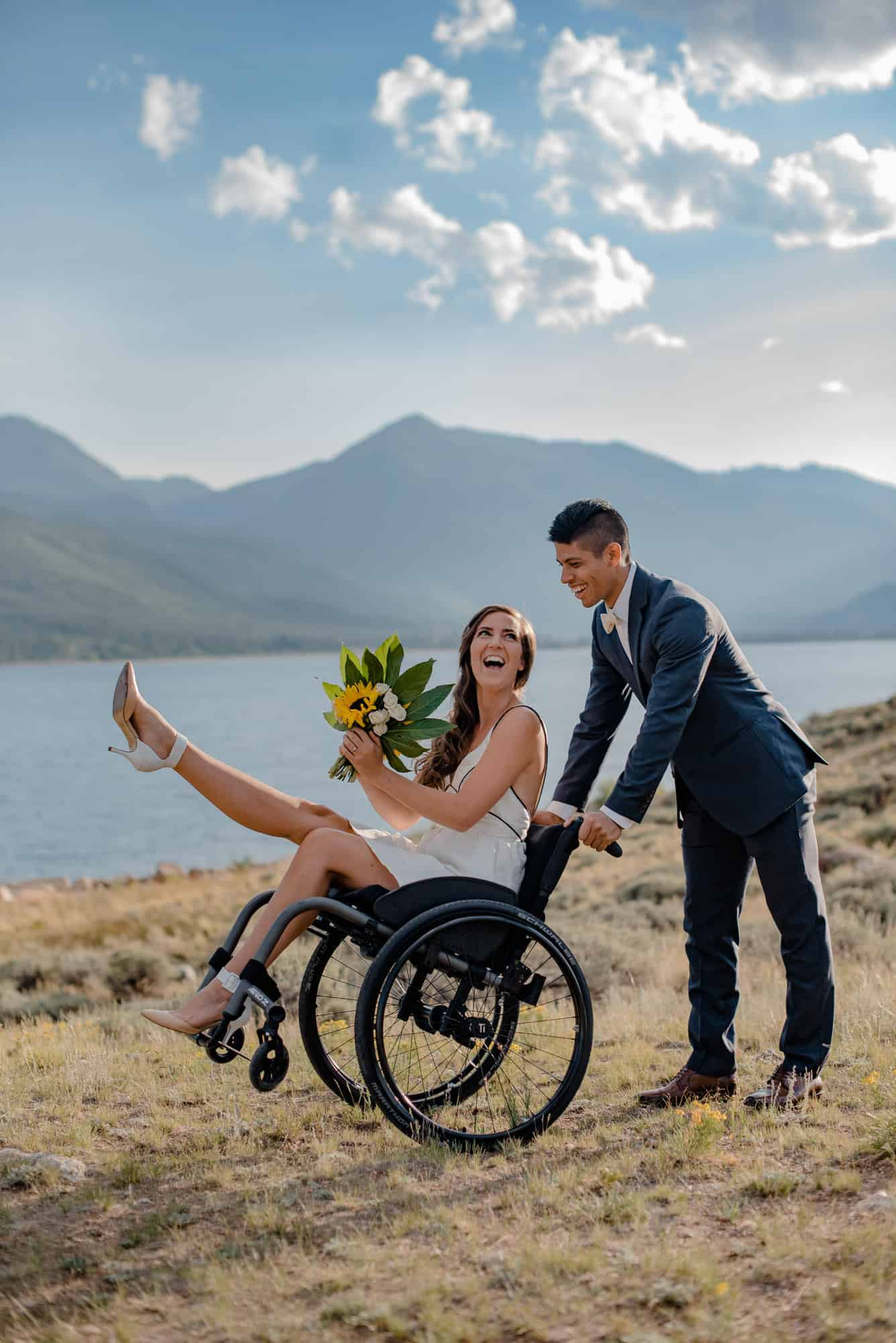 bride and group happy they are eloping during the pandemic as groom tilts brides wheelchair playfully and she kicks one leg out