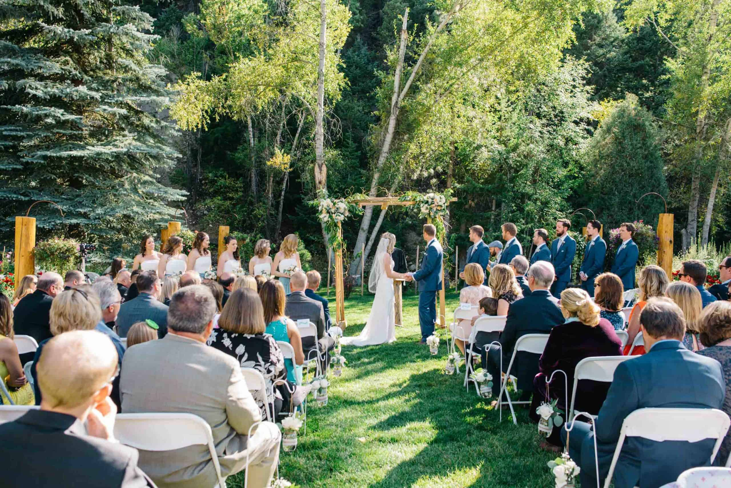 view of a wedding ceremony with guests on a green grassy area and trees in the background