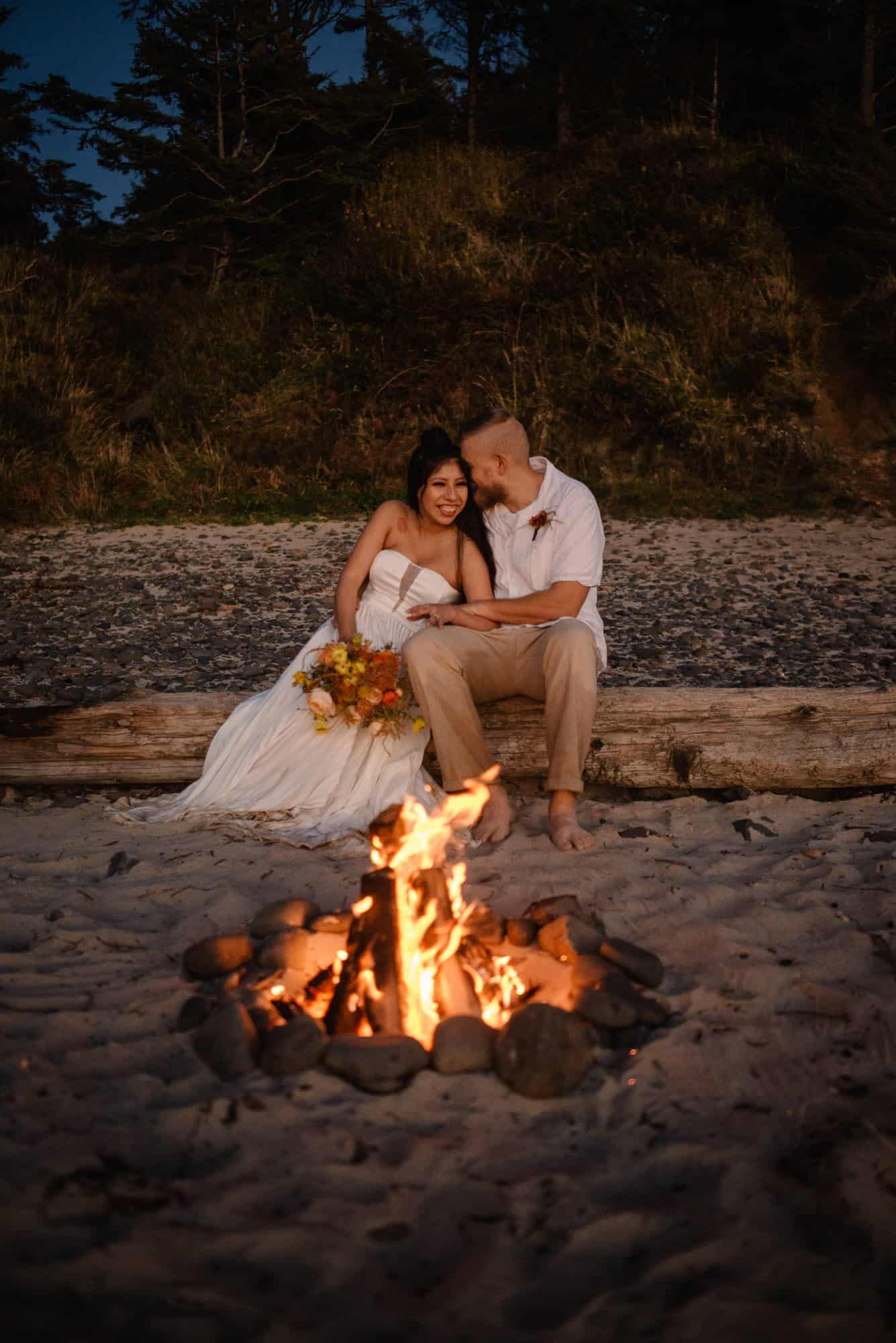 how to celebrate new year couple sitting around a beach side fire
