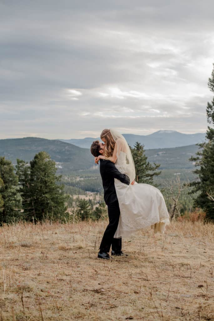 couple happy because they decided eloping as christians isn't selfish with groom picking up bride in the mountain field