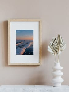 photo by Celebrate Again of ocean waves at sunset hanging on a wall in a wooden frame next to a paper plant decor for a yoga space at home