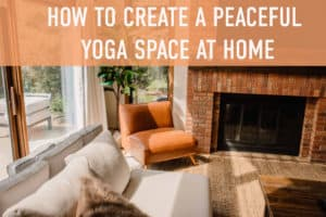 """how to create a peaceful yoga space at home"" text over a view of a living room with a cozy couch chair and fire place as the light streams in from the big windows"