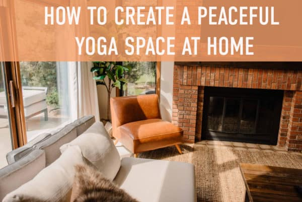 """""""how to create a peaceful yoga space at home"""" text over a view of a living room with a cozy couch chair and fire place as the light streams in from the big windows"""