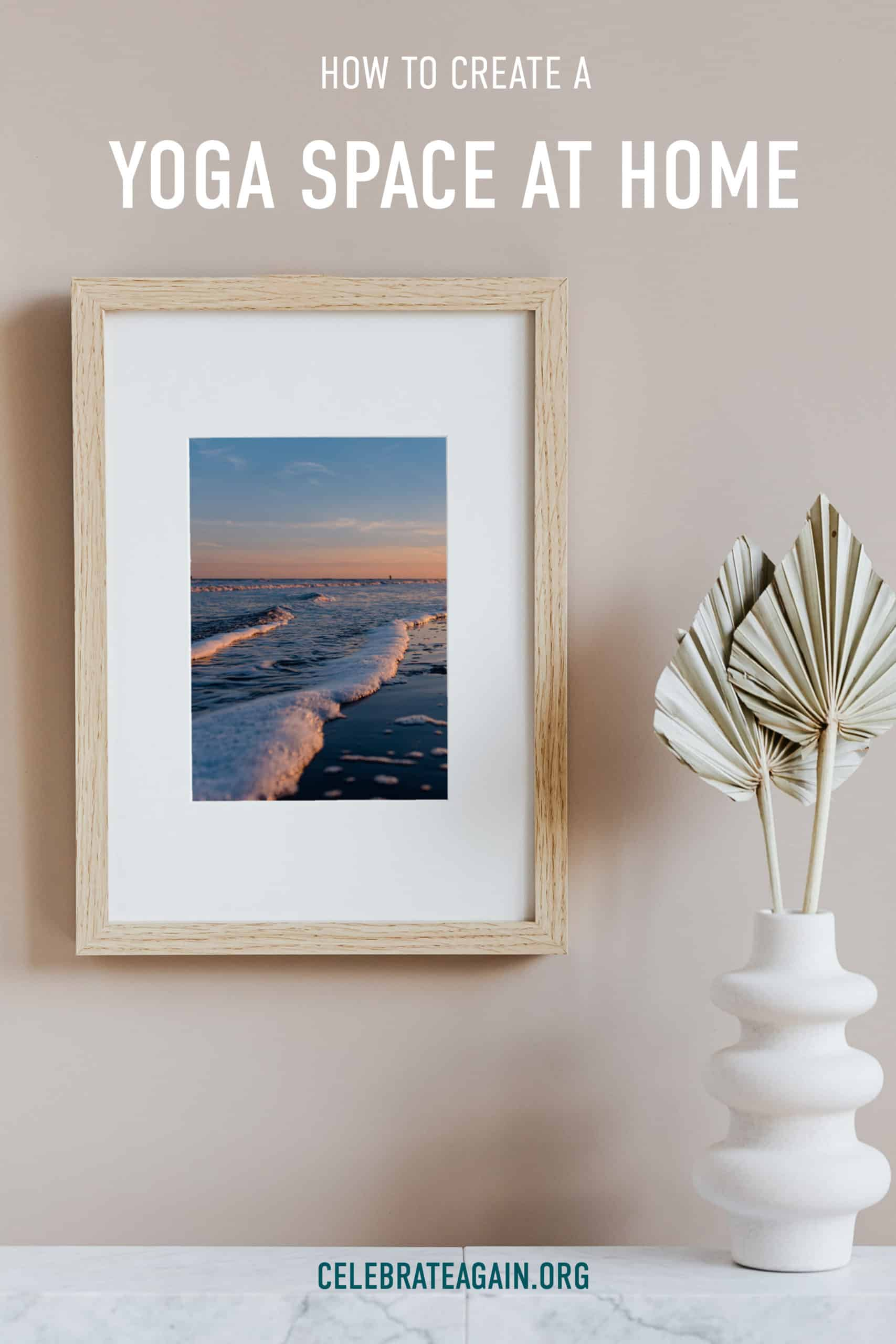 how to create a yoga space at home text photo by Celebrate Again of ocean waves at sunset hanging on a wall in a wooden frame next to a paper plant decor for a yoga space at home