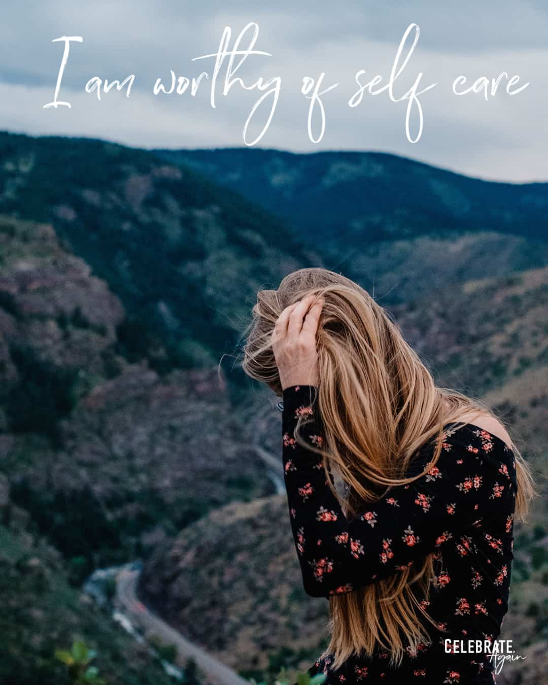 """I am worthy of self care"" as a mom quote by Celebrate Again view of a woman pulling her hair back on the top of a mountain cliff"