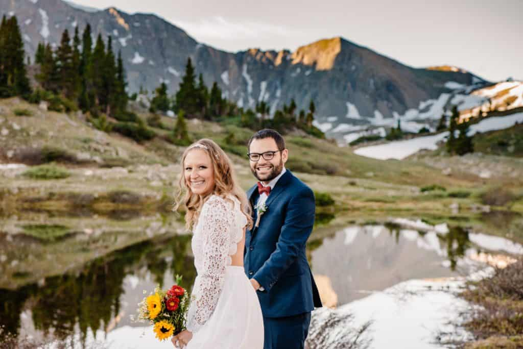 bride and groom smiling at the camera because they remembered everything on their packing list for elopement while getting married in the mountains