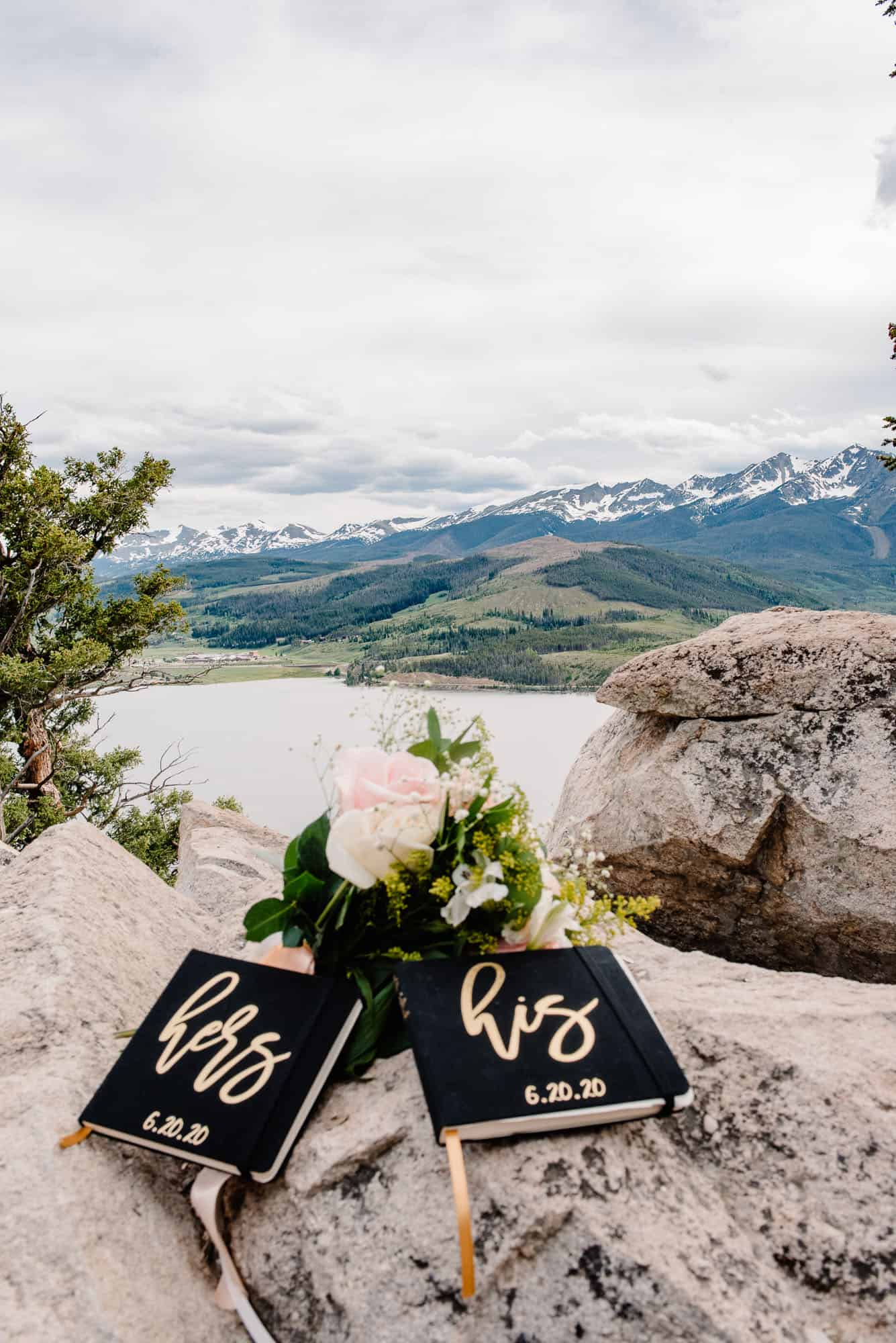 couples vow books on a rock over looking the mountains