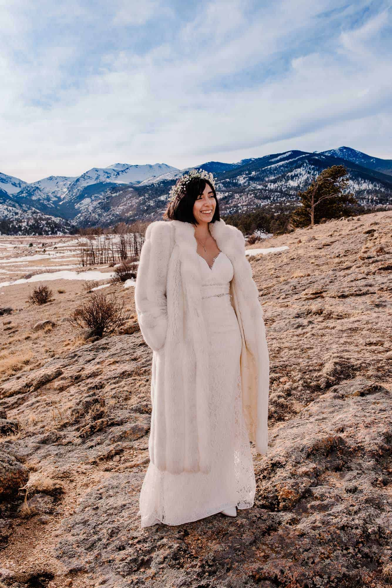 bride who added an over coat to her packing list for elopement over her dress standing in the mountains
