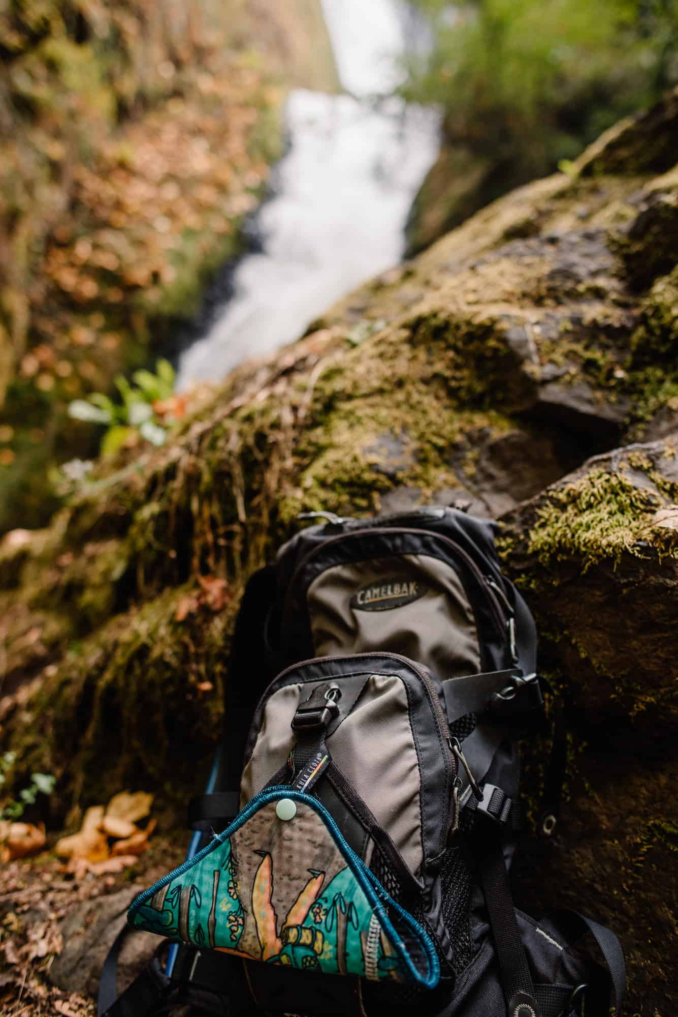 kula cloth on a backpack by a waterfall