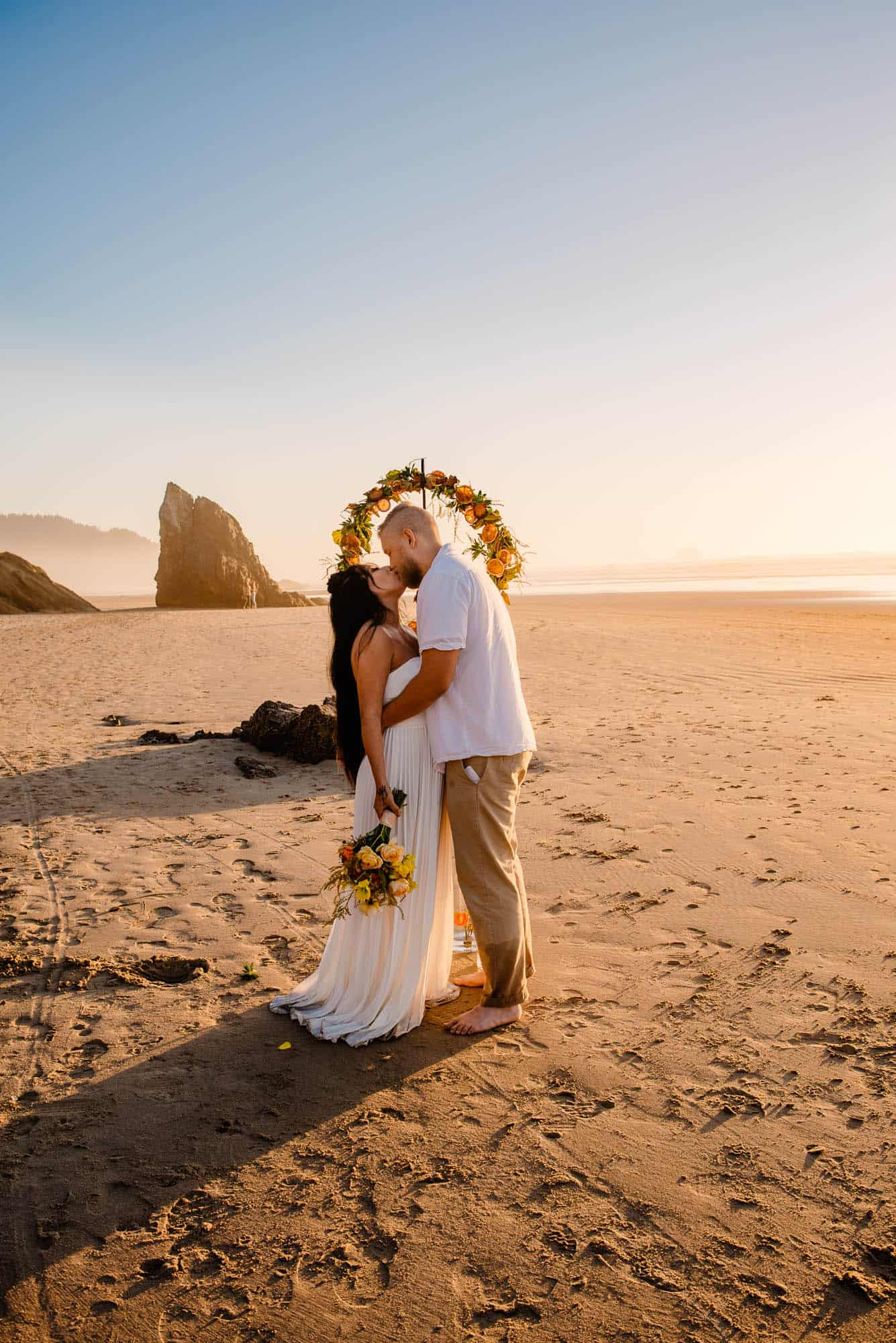 bride and groom kissing after ceremony on the beach in front of wedding arch