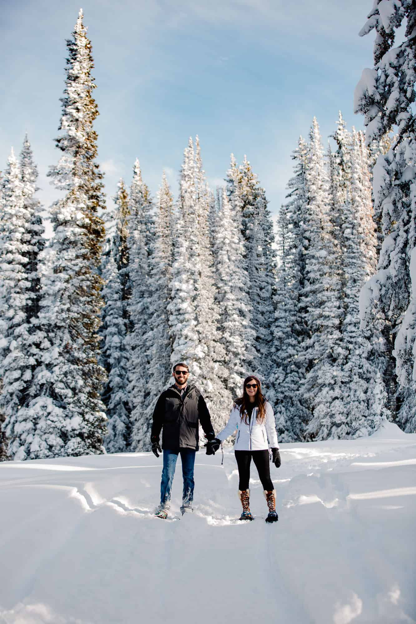 couple standing in snow in the middle of trees with sunglasses on because they remembered to add it to their elopement packing list