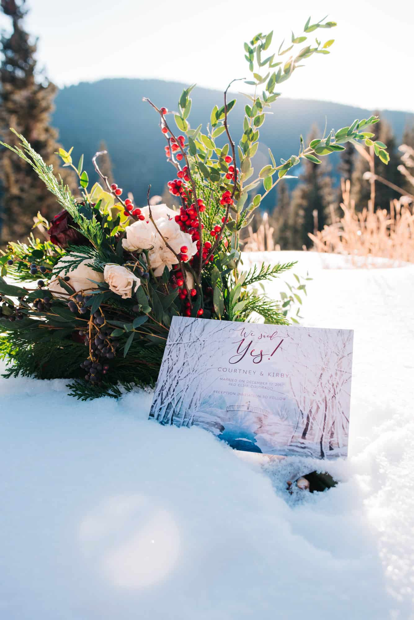 wedding invitation in the snow in the moutons next to flowers