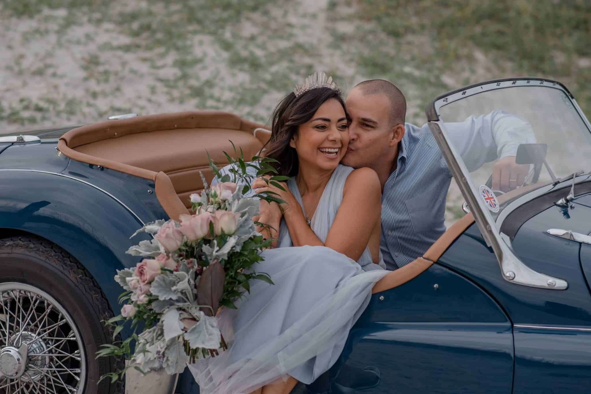couple in a vintage car with wife's legs out and husband kissing her cheek having followed this romantic things to do for wife idea list