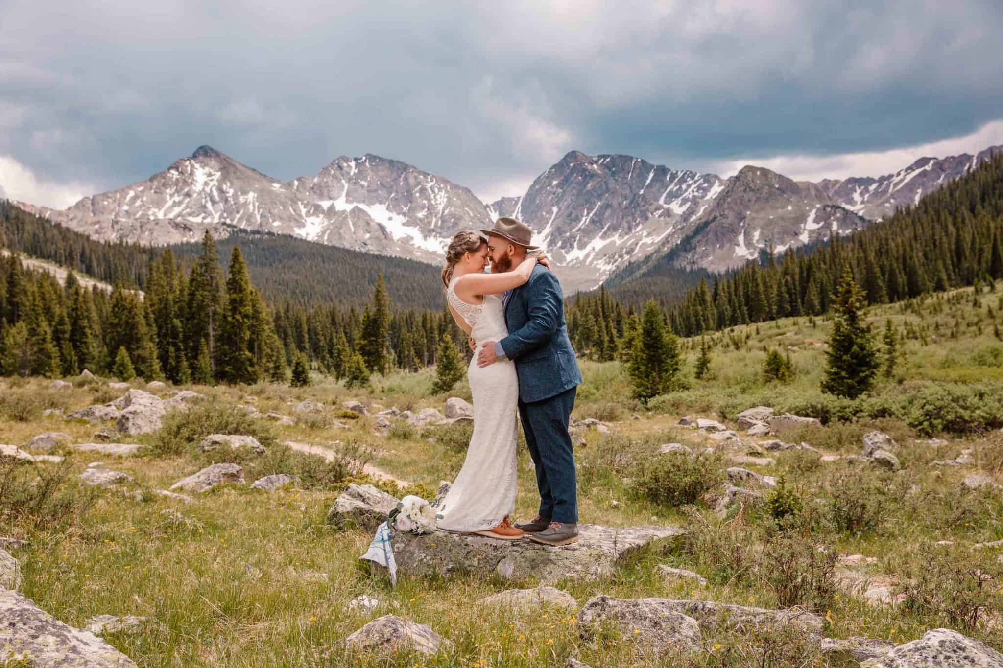 couple standing in the valley of the mountains hugging