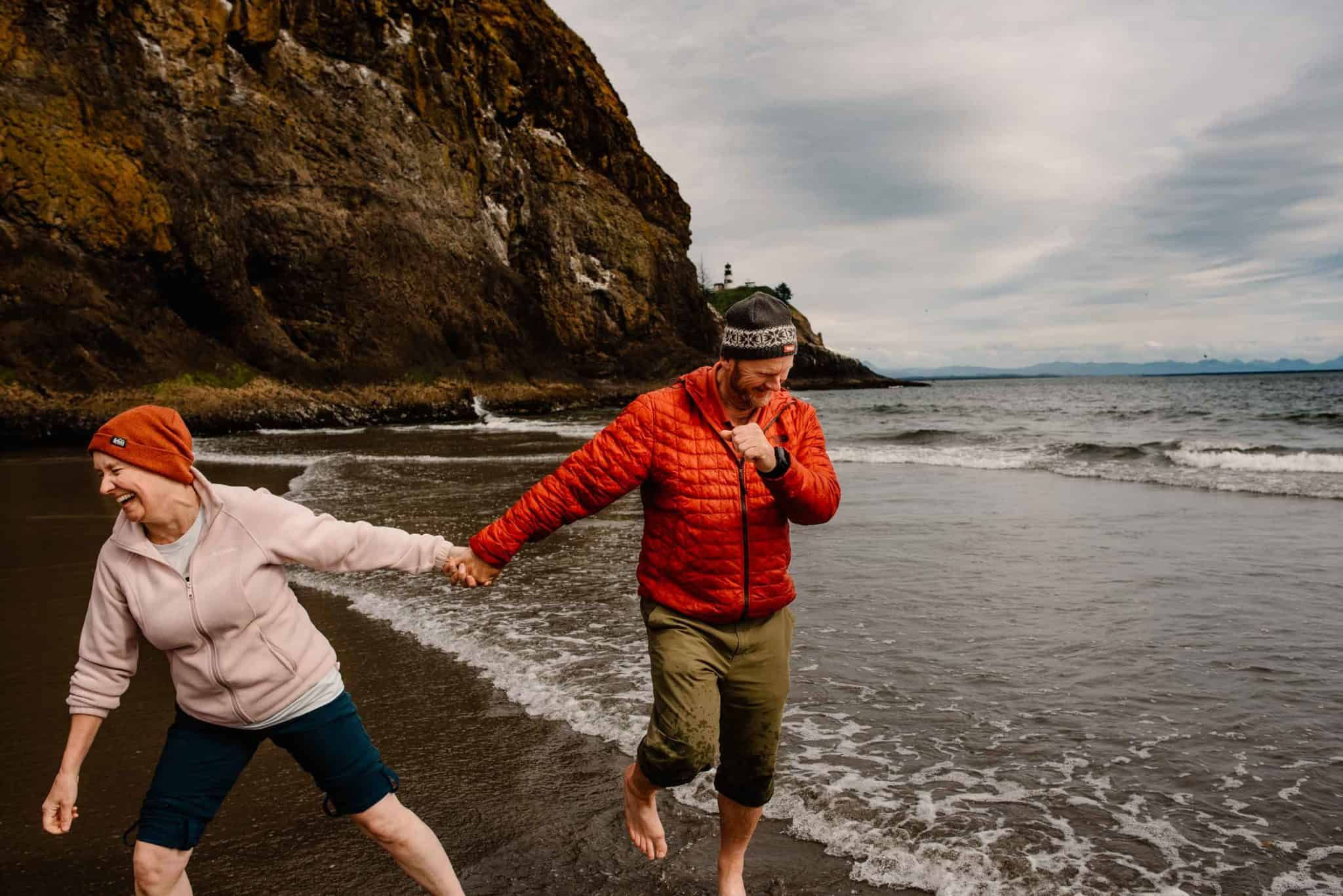 couple laughing and running away on the beach