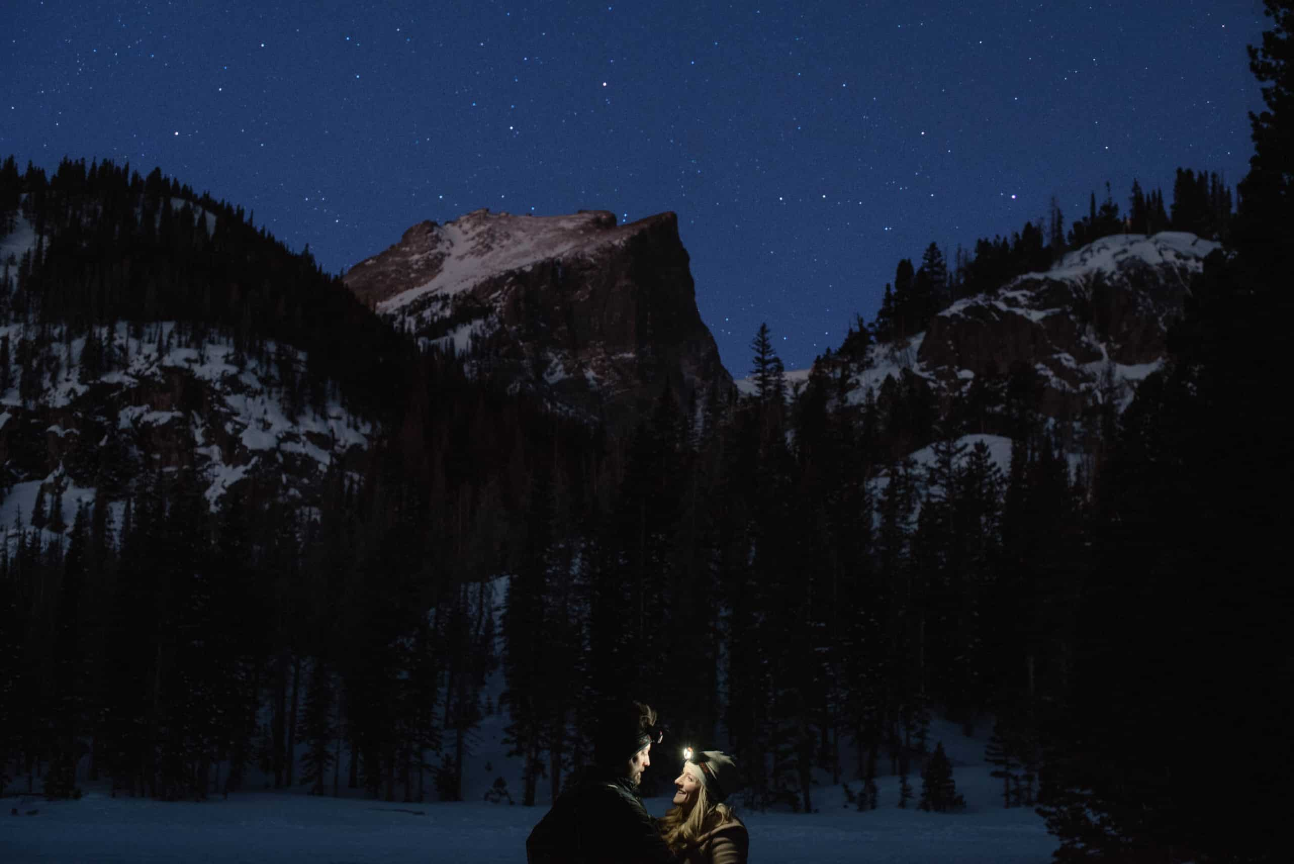 couple in headlamps near a mountain