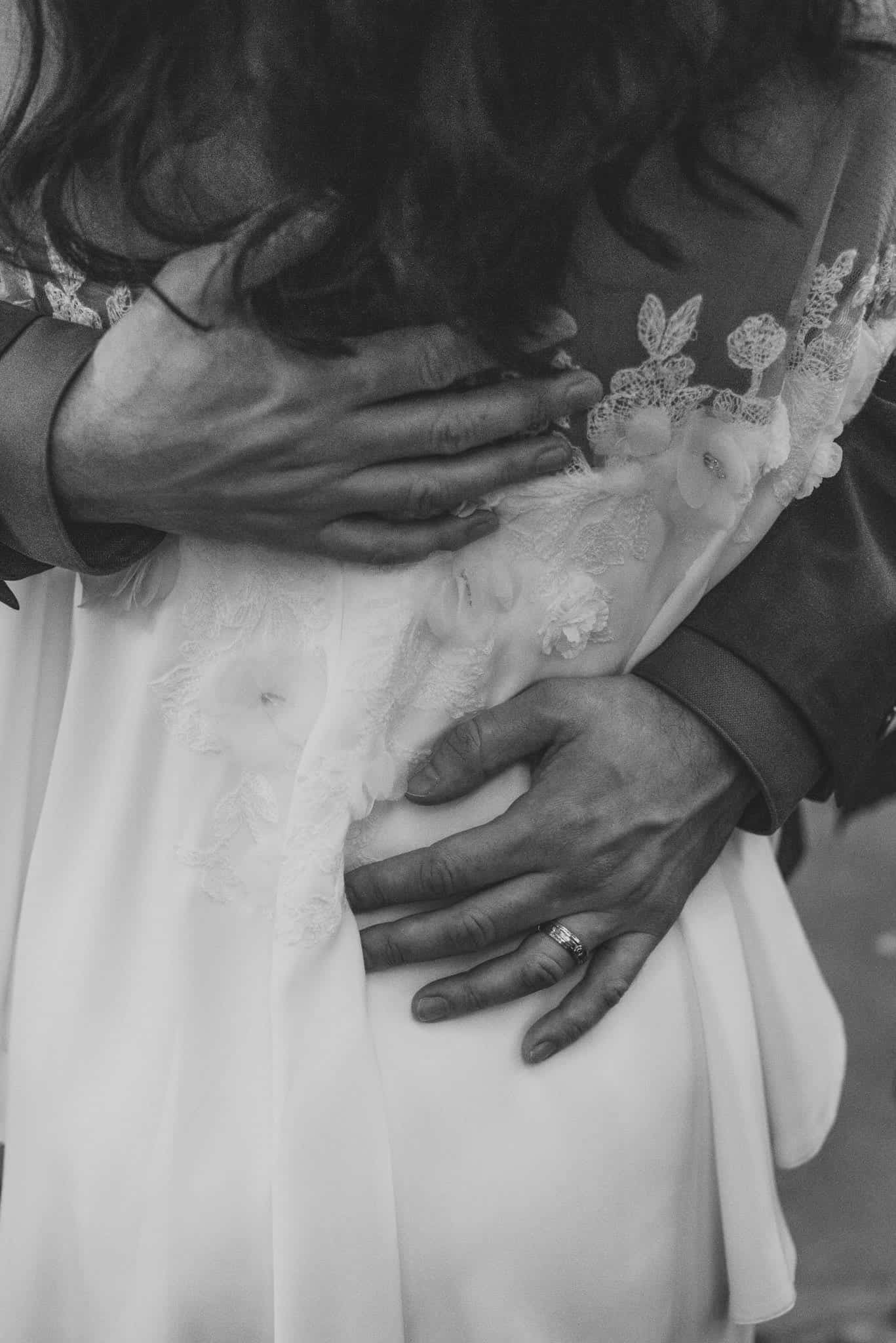 groom holding a bride romantically close a black and white photo