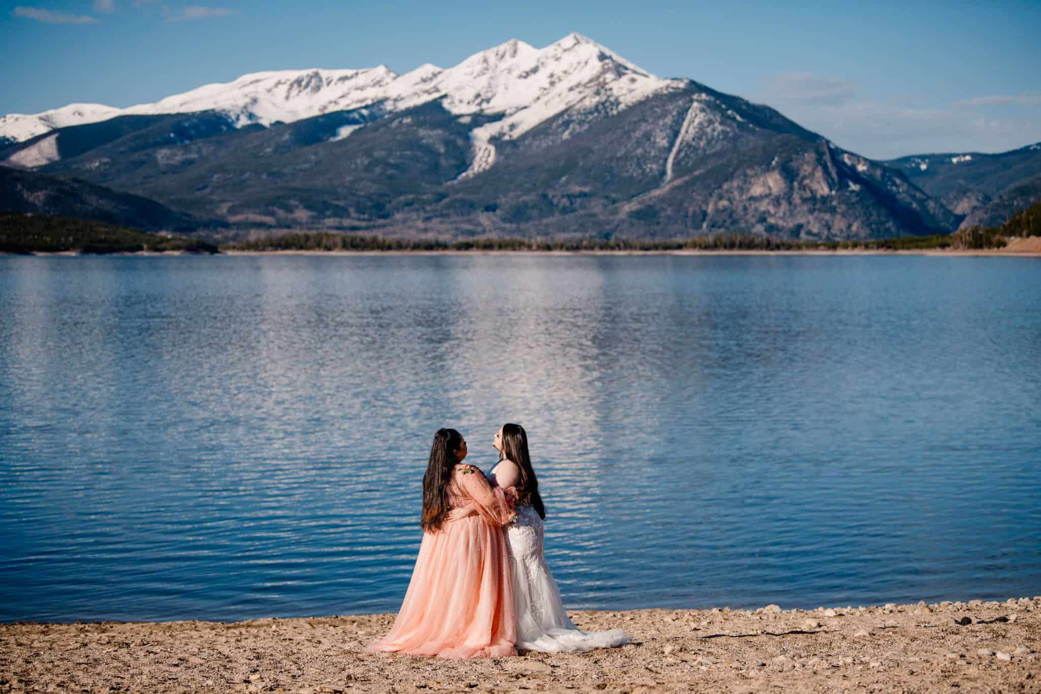 couple hugging at Lake Dillon in their wedding clothes on their elopement day