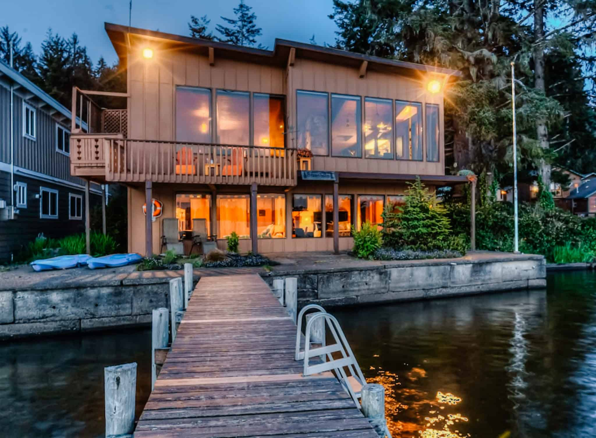 dock leading up to a wooden house with lights sparking on it