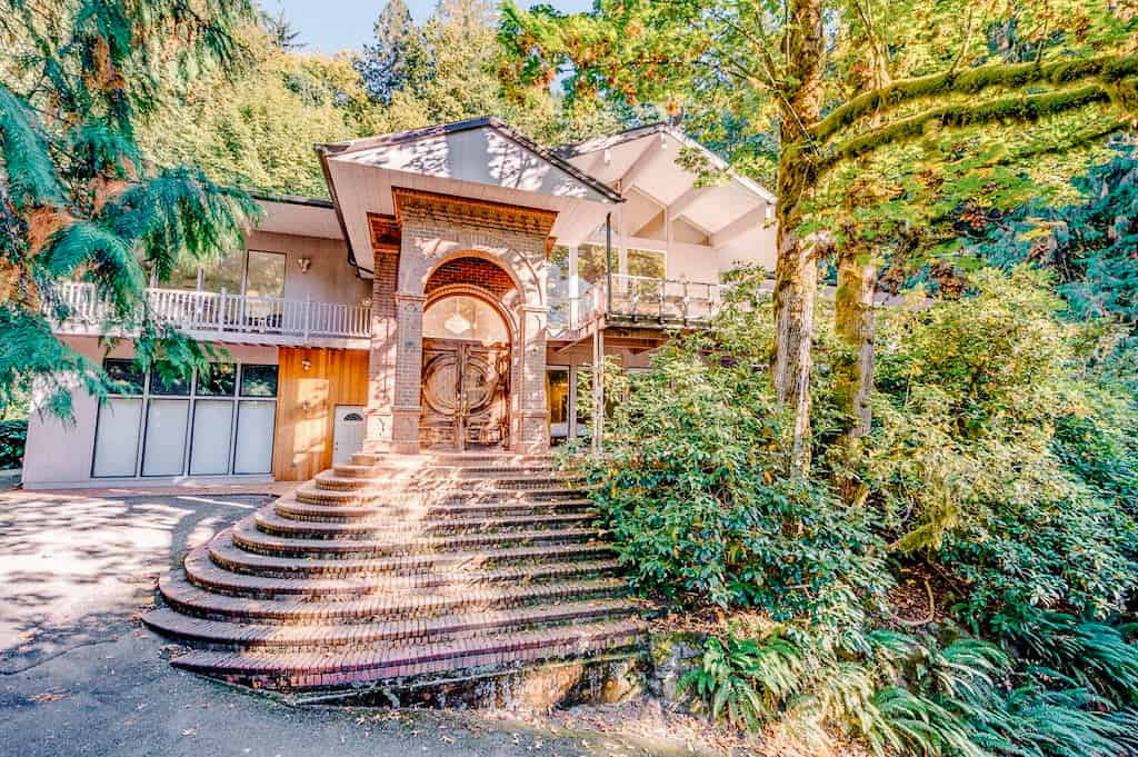 front steps of a luxury home with a luscious garden
