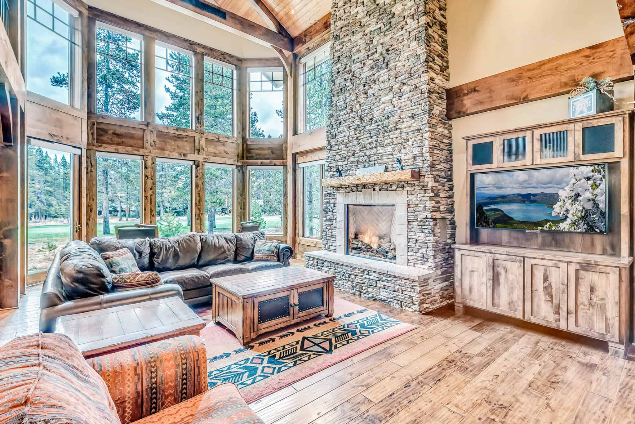 view of a modern luxury mountain home with a fire place and flat screen tv