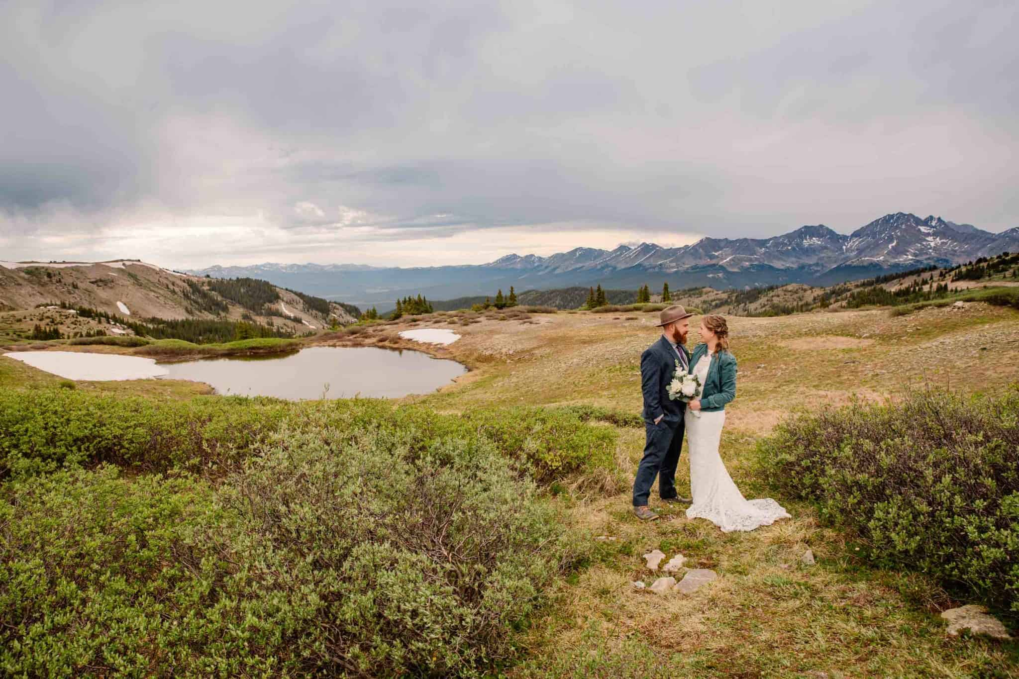 couple in Colorado on top of a moutain near an alpine lake with stunning views all around them