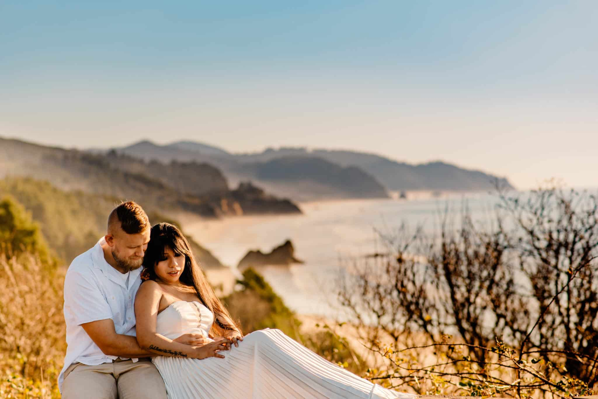 couple on a cliff edge with the mountains and beach behind them