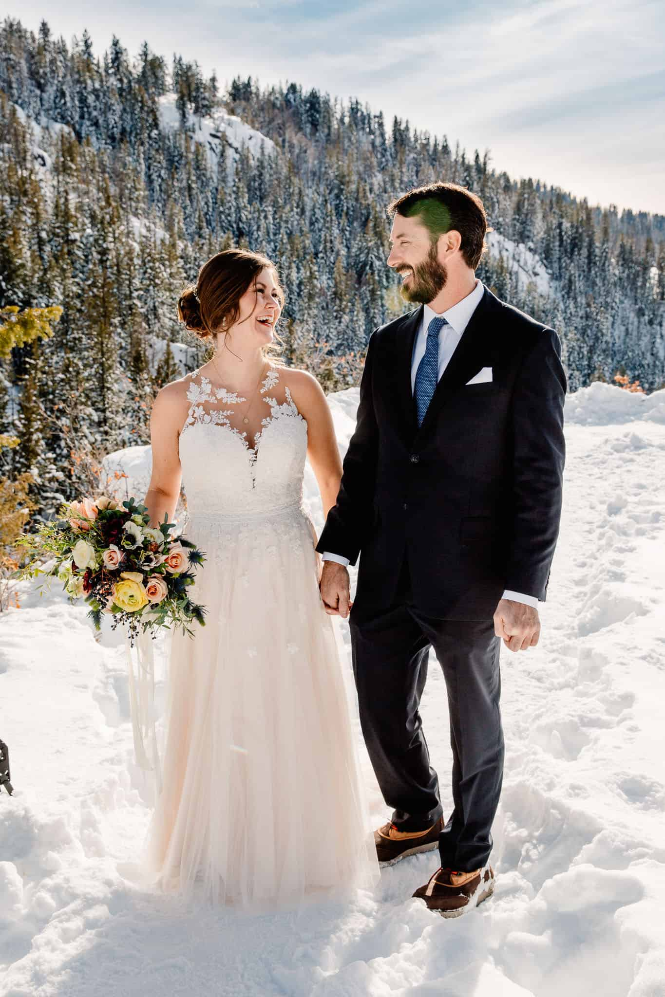 couple wearing nice wedding clothes while outside in the snow