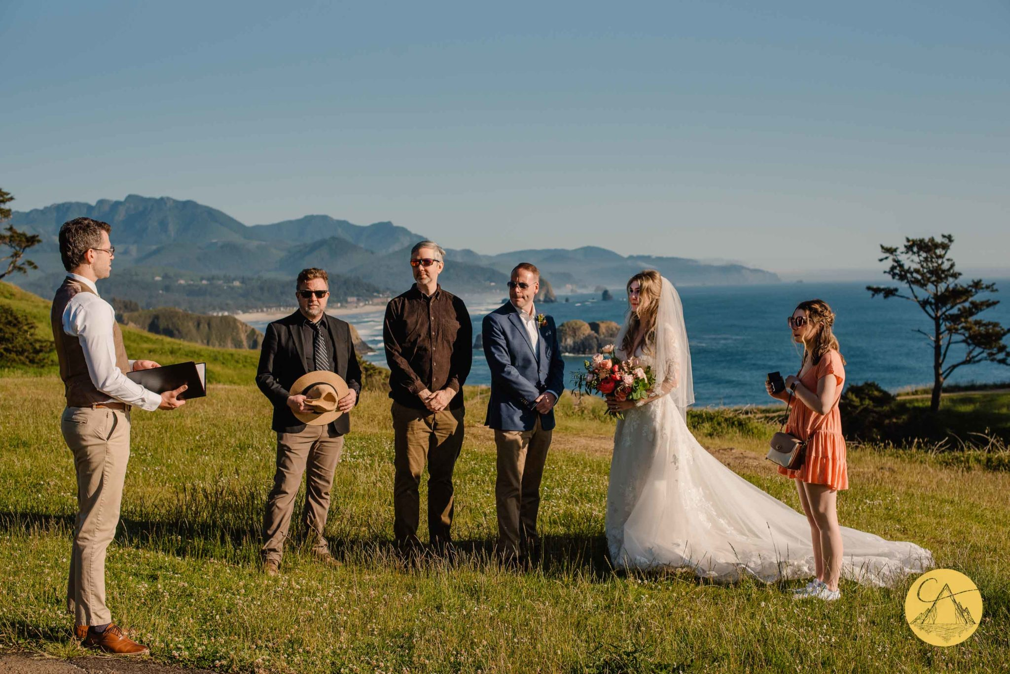 couple standing on the field of Ecola State Park having their wedding ceremony