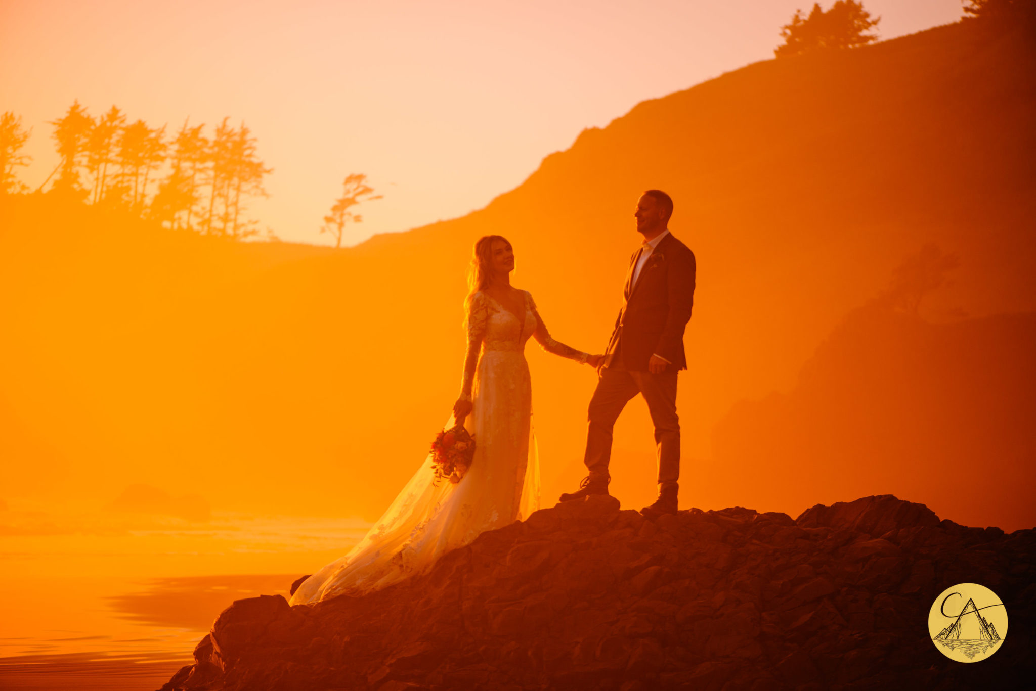 couple taking wedding photos on Ecola State Park beach with a view of couple standing on a rock with the Oregon coast shoreline in the background and the light is turned orange from the sun setting