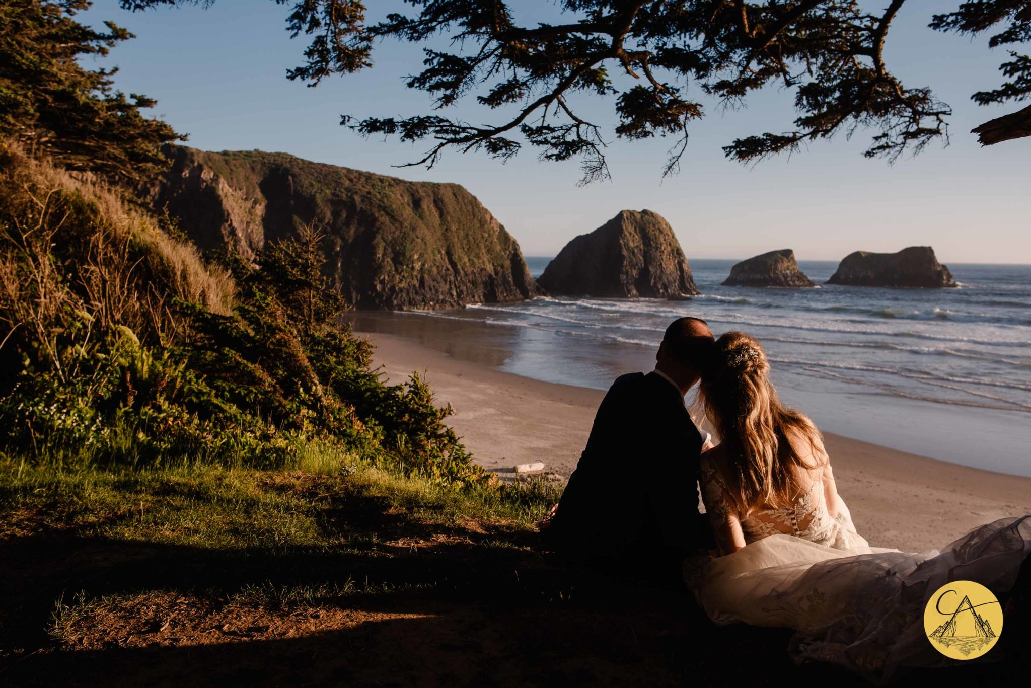 couple resting heads side by side on cliff edge of Ecola State Park after their wedding ceremony