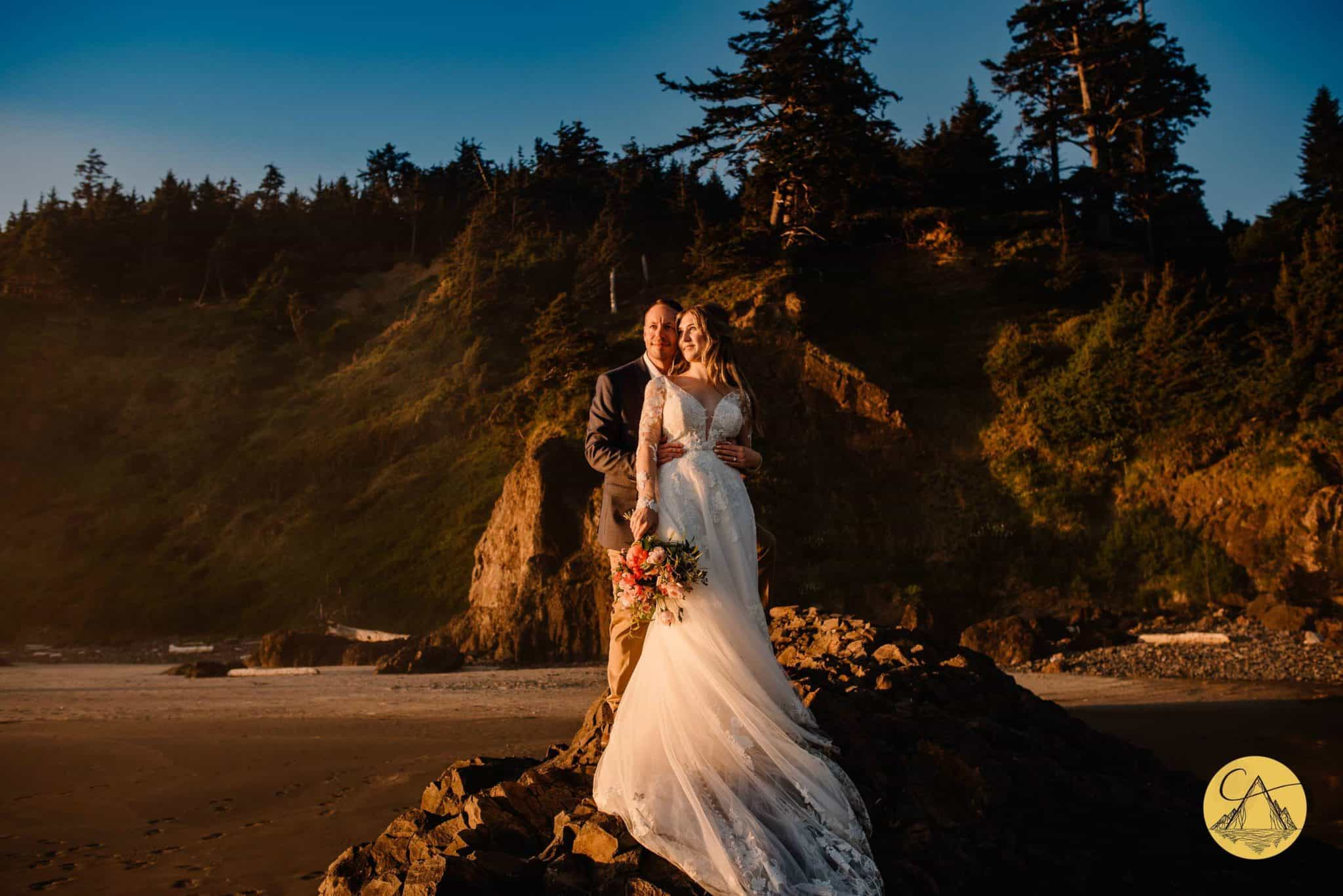 oregon elopement photographer taking photo of couple standing on the oregon coast as the sun shines on them and the cliffs are behind them