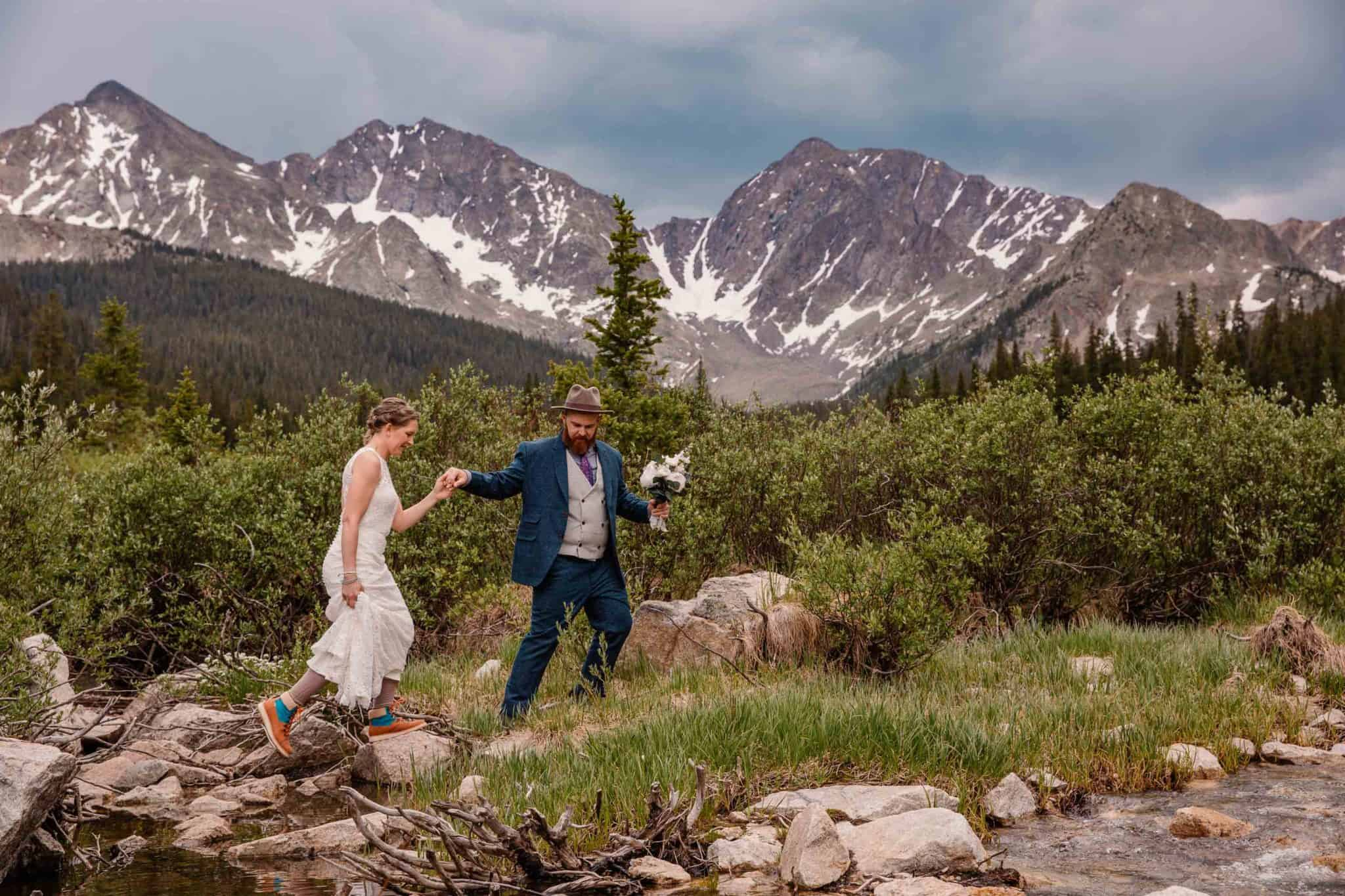 oregon elopement photographer taking photo of couple walking up a rock with the mountains behind them