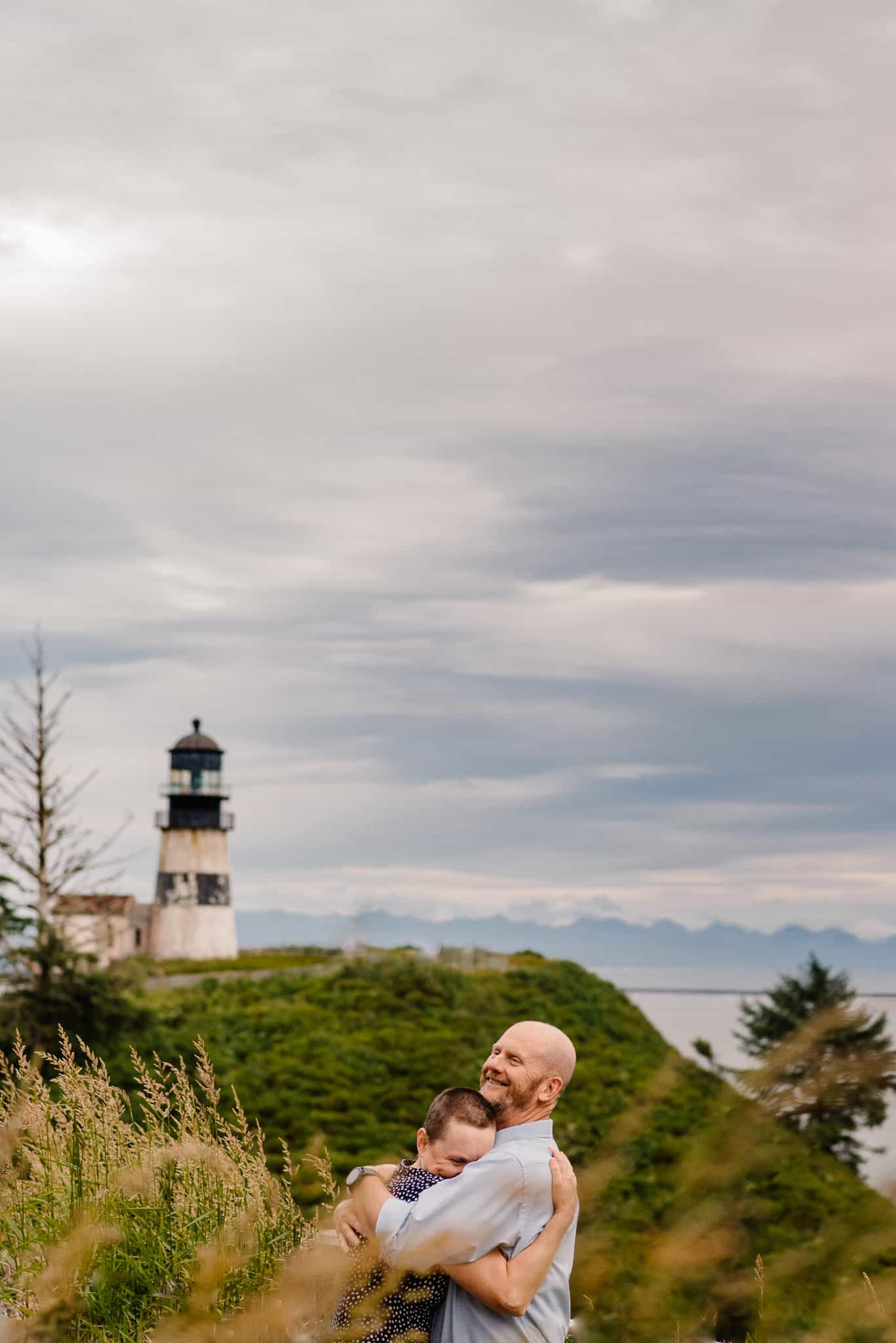 couples hugging near the ocean with a lighthouse in the background