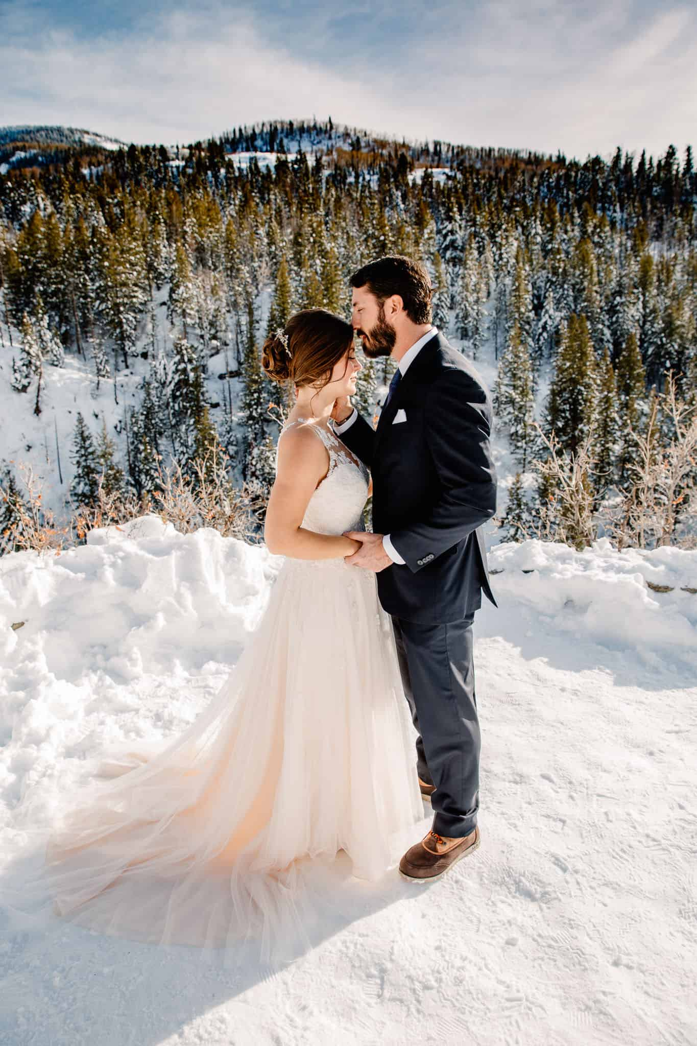 groom kissing bride forehead in the middle of the Oregon mountains in winter