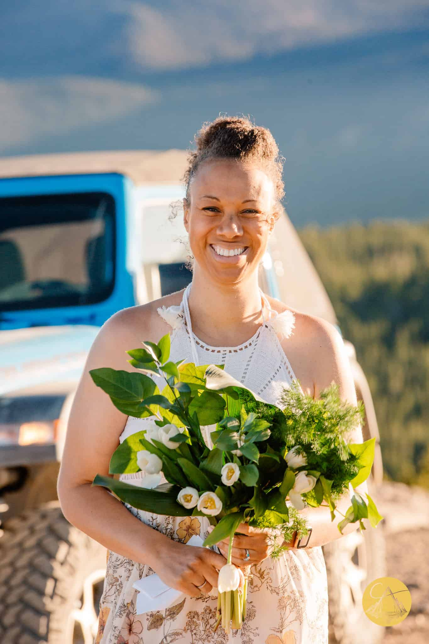 bride holding flowers at her 4x4 wedding with a jeep wrangler in the background
