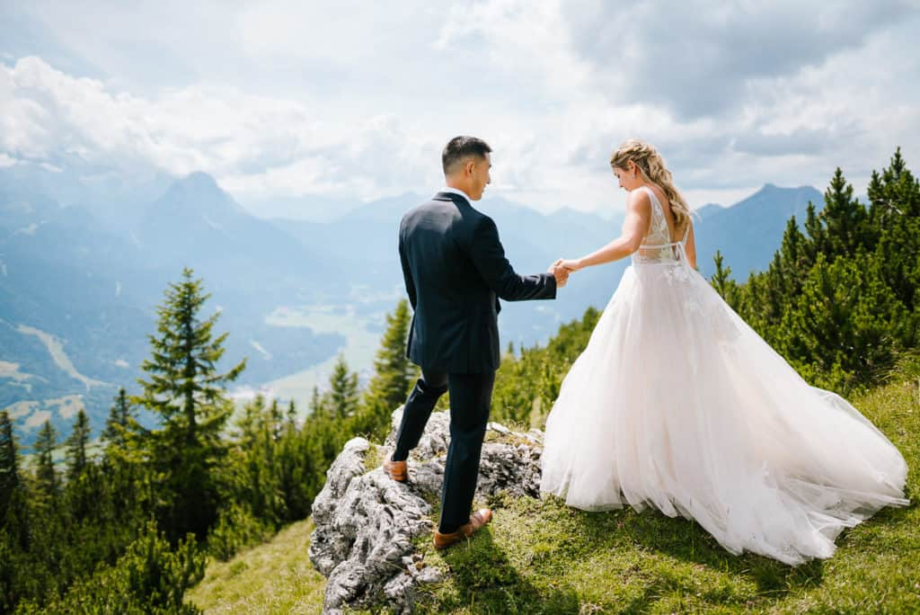 couple holding hands with the german alps in the background glad to elope in one of the best places in the world