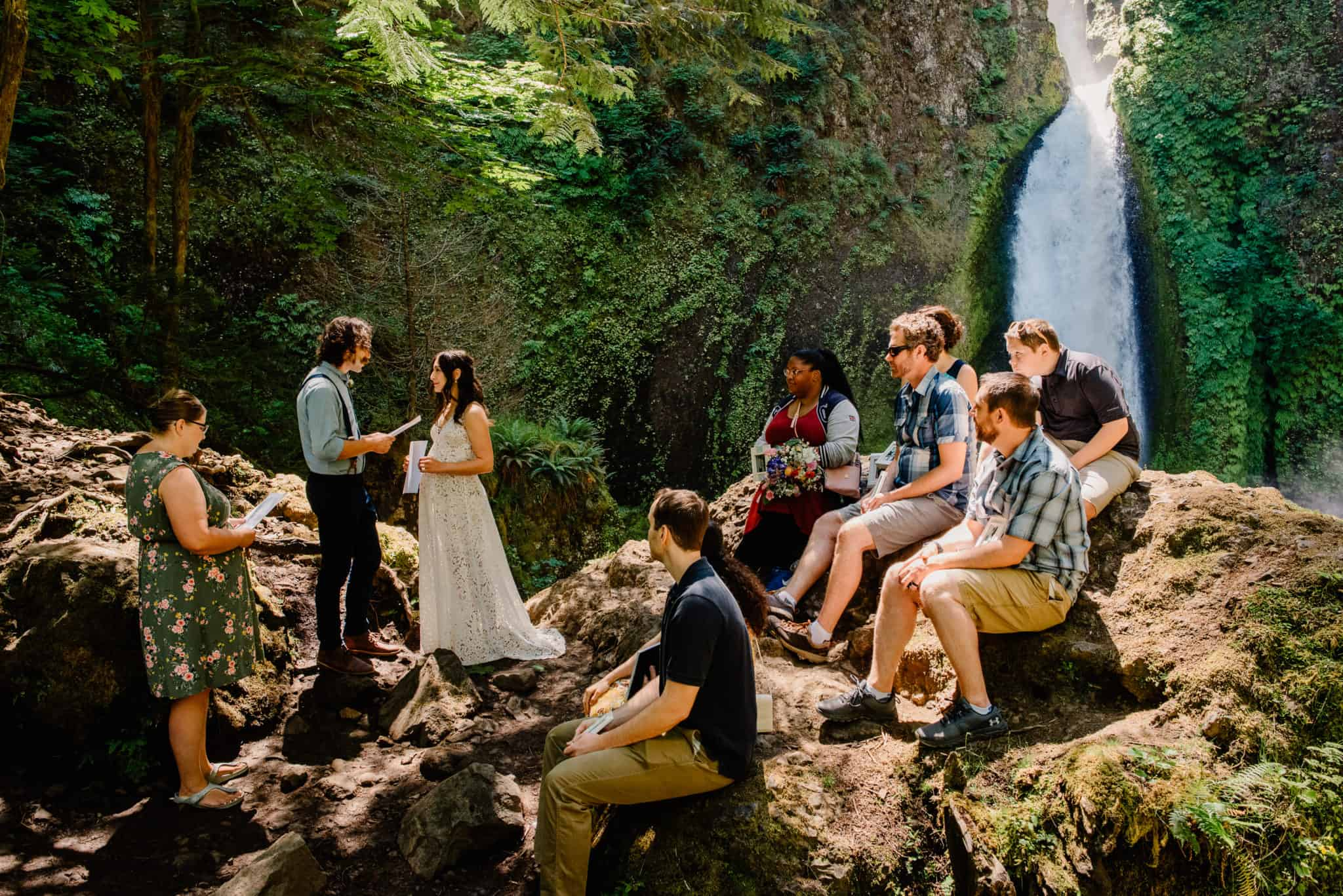 group of people sitting on a rock watching bride and groom exchange their vows in front of the wahclella falls in Oregon