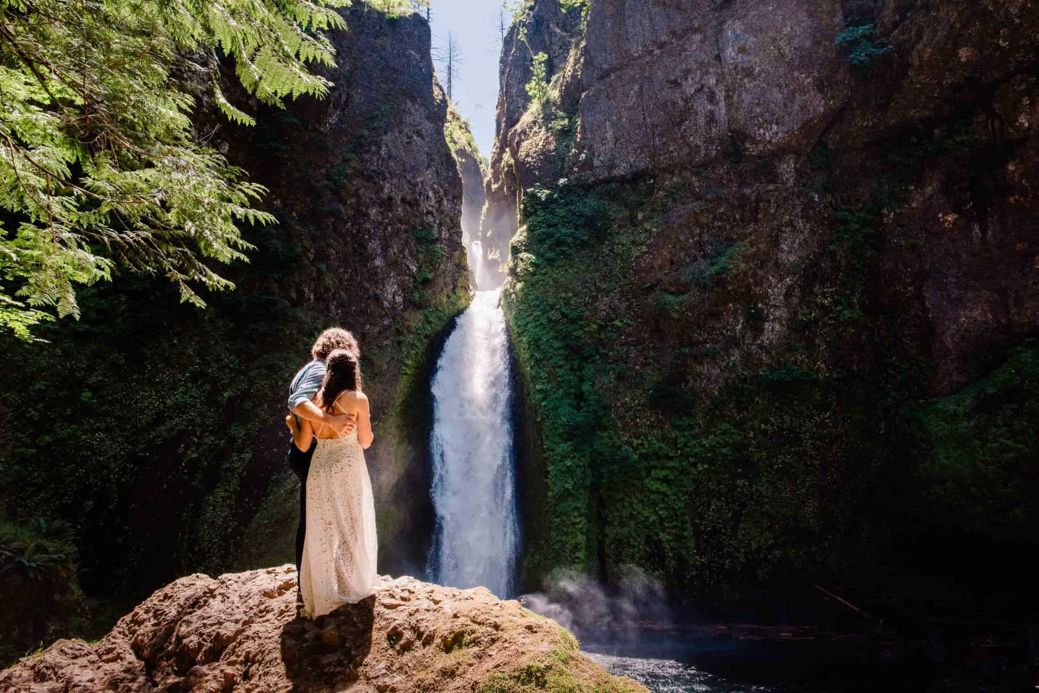 couple cuddling in front of Wahclella falls on their wedding day